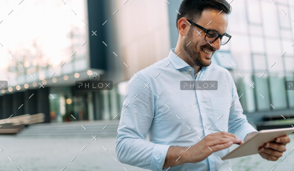 demo-attachment-1482-portrait-of-businessman-in-glasses-holding-tablet-AWVHCJU